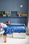 White bed with drawers in boy's bedroom with vintage-style toys and blue wall