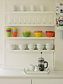 White and coloured crockery on white-painted, wall-mounted shelves above cafetiere on tray on worksurface
