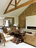 Armchairs and sofa in shades of brown in front of open fireplace in white chimney breast on brick wall