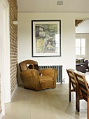 Vintage leather armchair below modern artwork on wall in corner