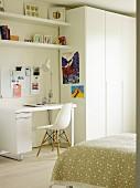 Schreibtisch mit Klassikerstuhl neben weißem Kleiderschrank im Jungedzimmer