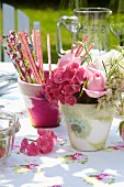 Romantic table arrangement with napkin decoupage pots, floral tablecloth and pink summer flowers