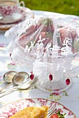 Hand-sewn, white lace fly cover over dish of strawberries on romantically set garden table