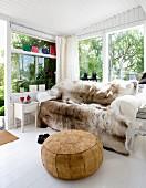 Gemütliches Sofa mit Rentierfell, davor Leder Sitzpouf in hellem Wintergarten