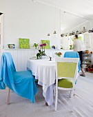 Round dining table with various chairs and white wainscoting in bright, cottage-style interior with view into kitchen