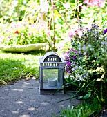 Laterne mit Teelicht auf Steinplatte in blühendem Garten