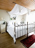 Double bed with metal frame, white bed linen and fabric canopy hanging from rods suspended from wooden ceiling