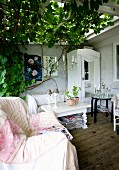 Comfortable armchair with blanket, coffee table and white-painted cabinet on veranda with climber-covered pergola