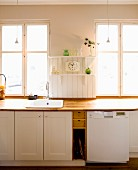 Kitchen counter with wooden worksurface and white cabinets below window in rustic interior