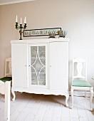 Halbhoher Schrank weiss lackiert, in ländlichem Stil, seitlich Stühle in Weiss, mit geschwungenen Beinen