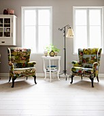 White-painted side table and standard lamp with wrought iron frame between armchairs with farmyard-patterned covers below windows