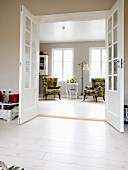 Open double doors with view into lounge with armchairs below windows
