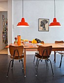 Glass bowls on extendible table with retro school chairs and orange pendant lamps in dining area
