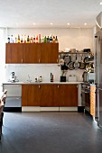 Retro kitchen with teak and stainless steel doors, various pans and cooking utensils hanging from wall-mounted shelf