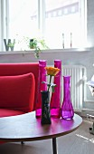 Arrangement of various vases on small retro table next to red sofa in living area