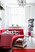 Red designer sofa, stacked cushions on floor, magazine rack and side table in renovated period building with retro ambiance