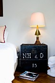 Eclectic table lamp on vintage wooden trunk used as bedside table