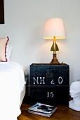 Eklektische Tischlampe auf Vintage Holzkiste als Nachtkästchen