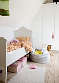 White, child's bed with vintage-style frame and beanbag on wooden floor in front of white fitted wardrobes
