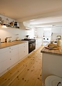 Kitchen counter with white base units in spacious kitchen with wooden floor and open doorway leading into utility room