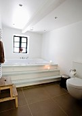 Modernes Bad mit braunen Bodenfliesen, Stufen vor eingebauter Badewanne am Fenster