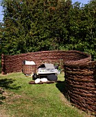 Curved wicker garden fence screening sun lounger in garden