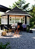 Holz Pavillon schwarz gestrichen mit weissen Sprossenfenstern, davor farbige Klappstühle auf Kiesboden