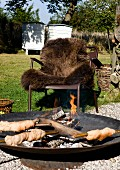 Campfire bread in fire bowl in front of outdoor armchair with brown fur blanket in garden