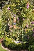 Pink foxgloves and garden ornaments in idyllic garden
