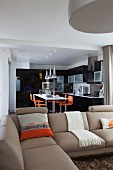 Beige sofa in front of open-plan fitted kitchen with black fronts and orange bar stools at counter