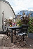 Seating area with modern, black metal furniture, wooden deck and planters on urban roof terrace