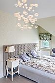 Doppelbett mit gepolstertem Kopfteil und klassische Leuchten auf Antikkommoden in der Ecke eines Dachzimmers; Hängeleuchte mit Glasbubbles im Vordergrund