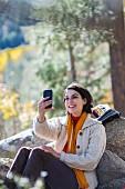 Frau in Wanderkleidung sitzt an Felsen gelehnt auf Waldlichtung & macht Selfie