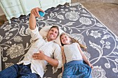 Father and daughter lying on rug taking selfie