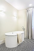 Free-standing designer bathtub and floor-mounted taps in elegant bathroom with floor-length curtains and black and white mosaic floor