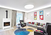 Brightly coloured scatter cushions on grey sofa and armchairs, round colourful rugs in front of fireplace and pop-art-style pictures