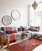 Oriental atmosphere with colourful fabrics, grey sofa set, metal trays on wall and typical Moroccan pendant lamps