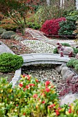 Stone bridge spanning gravel bed in Japanese-style garden