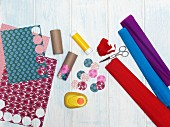Utensils for crafting a wind chime: cardboard tubes, coloured paper, crepe paper and circle punch