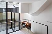 Blick durch Verglasung auf Wohnzimmer mit Sofa und Schreibtisch im Anbau