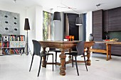 Kitchen-dining area with antique table, plastic chairs, charcoal kitchen counter, open-fronted shelves and standard lamp