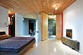 Puristischer Schlafraum in moderner Architektur; rustikale Steinplatte unter dem Kaminfenster