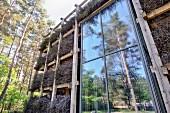 Bundles of brushwood on wooden rack against facade of architect-designed house