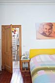 Doppelbett mit gelbem Kopfteil, Bettwäsche in Patchwork Muster, daneben kleiner Nachttisch und offene Tür mit Blick auf Treppe
