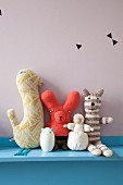 Soft toys on blue-painted shelf