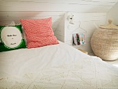Rustic, white, attic bedroom with crocheted bedspread, scatter cushions and large basket