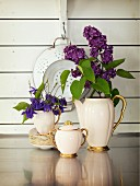 Elegant coffee set decorated with flowers in front of vintage colander