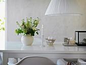 Romantische Tischdekoration mit Kerzenlicht und Blumenstrauß auf glänzender weißer Tischplatte