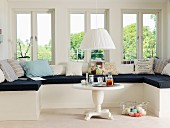 Window seat with black seat cushion and patterned scatter cushions in renovated, white, country-house interior
