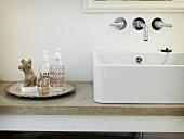 Weißes Aufsatzbecken auf Steinwaschtischplatte mit nostalgischem Silberteller, zeitgenössischem Seifenspender und Miniatur Steintorso